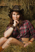 Cowgirl sitting on hay in the stable — Stock Photo