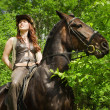 Cowgirl on brown horse — Stock Photo