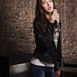 Stock Photo: Rock babe singing into a microphone
