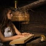 junges Mädchen sitzend mit alten Buch in dunklen Innenräumen — Stockfoto