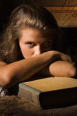 Young girl sitting with old book in a dark interior — ストック写真