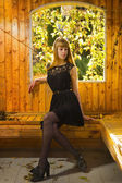 Pretty blonde sitting in the arbor — Stock Photo