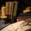 Old books and candles on wooden table — Foto Stock
