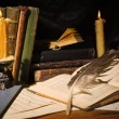 Old books and candles on wooden table — Foto de Stock