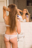Girl dries hair the hair dryer — Stock Photo