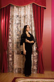 Elegant brunette in a luxurious interior. — Stock Photo