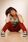 Besuty 女性赤ジーンズとスニーカーの床に座って — ストック写真