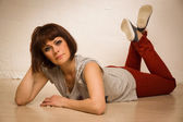 Besuty woman in red jeans and sneakers lying on floor — ストック写真