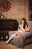 Young girl sitting by the fireplace — Stockfoto
