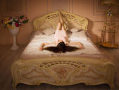 Young girl lying on the bed in an elegant bedroom — Stock Photo