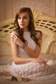 Elegant girl in evening dress in an elegant bedroom — Stock Photo