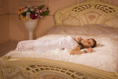 Young girl on the bed in an elegant bedroom — Stock Photo