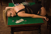 Lifeless woman in a luxurious lingerie lying on the casino table — Stock Photo