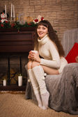 Young girl sitting by the fireplace — Stock Photo