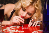 Sensual blonde lady in black sniffing cocaine (Imitation) — Stock Photo