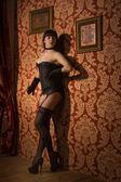 Piin-up girl wearing black underwear in the dark interior — Stock Photo