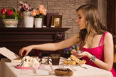 Cheerful woman eating sweets — Stock Photo