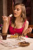 Cheerful woman eating pie — Stock Photo