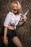 Rock babe singing into a microphone — Stock Photo