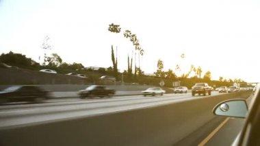 Trafic venant en sens inverse sur une autoroute américaine au coucher du soleil — Vidéo