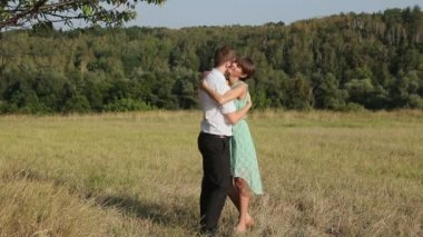 Young couple hugging on the yellow grass — Stock Video