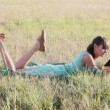 Young woman browsing in Internet with tablet lying on the grass — Stock Video #12695744