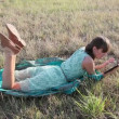 Young woman browsing in Internet with tablet lying on the grass — Stock Video #12757613