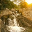 Waterfall in summer mountain at sunset - Stock Photo
