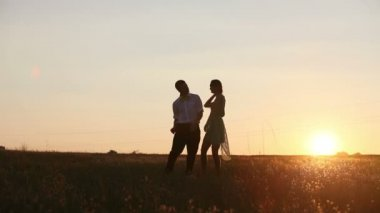Young couple silhouettes dancing on the field at sunset — Stock Video