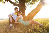 Young couple lying under the tree — Stock Photo