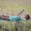 Young woman browsing in Internet with tablet lying on the grass — Stock Video #13845193