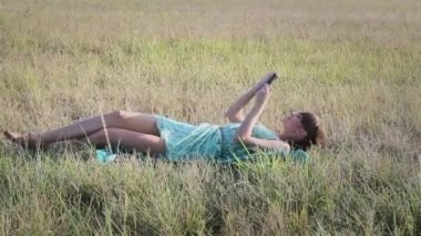 Young woman browsing in Internet with tablet lying on the grass — Stock Video
