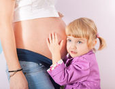 Daughter hugging mother's pregnant belly — Stock Photo