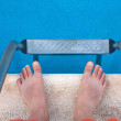 Stockfoto: Man's legs and ladder near pool