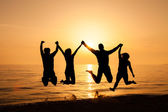 Four friends jumping on the beach — Stock Photo