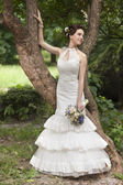 Young bride with bouquet near tree — Stock Photo