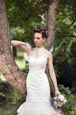 Молодая невеста с букетом возле дерева — Стоковое фото