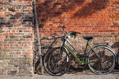 Bicycles on the pavement near brick wall — Stock Photo
