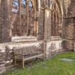 Medieval abbey yard with wooden bench — Stock Photo