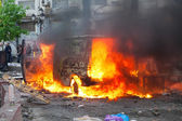 Burning car in the center of city during unrest — Stock Photo