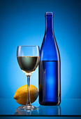 Blue wine bottle and lemon — Stock fotografie