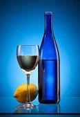 Blue wine bottle and lemon — Stock Photo