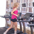 Attractive woman running on treadmill — Stock Photo