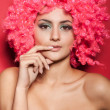 Beautiful woman in pink wig on red — Stock Photo