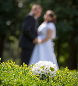 Wedding bouquet and couple — Stock Photo