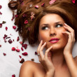 Beautiful young woman with flowing hair and flowers — Stock Photo