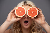 Smiling woman holding two grapefruits in hands — Stock Photo