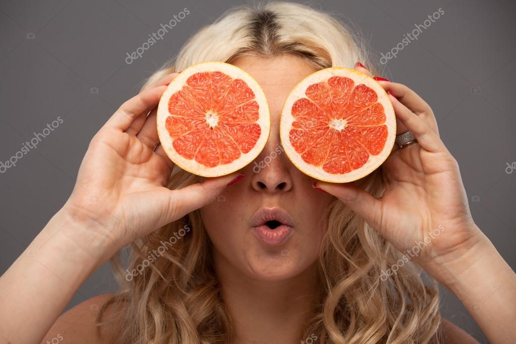 Smiling woman holding two grapefruits in hands — Stock Photo #13928524