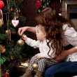 Happy mother decorating christmas tree with her baby - Stock Photo
