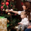 Happy mother decorating christmas tree with her baby — Stock Photo #15658499